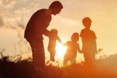 A silhueta do pai feliz com árvore caçoa no céu do por do sol Foto de Stock