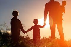 A silhueta do pai feliz com árvore caçoa no por do sol Fotografia de Stock Royalty Free