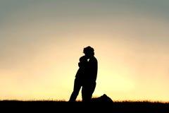Silhueta do pai Lovingly Kissing Child na testa em Sunse Fotos de Stock