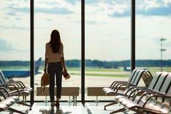 Silhueta do passageiro fêmea da linha aérea em um avião de espera do voo da sala de estar do aeroporto foto de stock