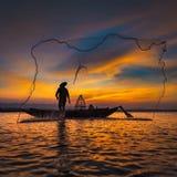 Silhueta do pescador asiático no barco de madeira na ação Foto de Stock