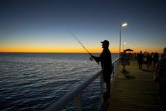 A silhueta do pescador com a haste do chapéu e dos peixes que está na pesca da doca do mar no por do sol com o céu alaranjado bon Fotografia de Stock