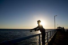 A silhueta do pescador com a haste do chapéu e dos peixes que está na pesca da doca do mar no por do sol com o céu alaranjado bon Imagem de Stock Royalty Free