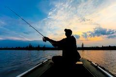 Silhueta do pescador com a vara de pesca no barco inflável no nascer do sol e nos lances uma atração para peixes de travamento Fotografia de Stock