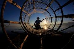 Silhueta do pescador do intha contra o céu do por do sol imagem de stock