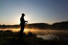 Silhueta do pescador em peixes de travamento do alvorecer no rio Manhã fria e névoa do verão sobre o rio fotos de stock royalty free