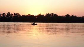 Silhueta do pescador em peixes de travamento do barco no rio no por do sol da noite do fundo video estoque