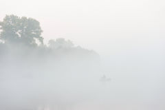 Silhueta do pescador em um rio na manhã enevoada fotografia de stock
