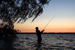 Silhueta do pescador no por do sol Imagem de Stock
