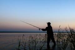 Silhueta do pescador no por do sol Fotografia de Stock
