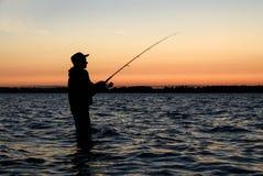 Silhueta do pescador no por do sol Imagem de Stock Royalty Free