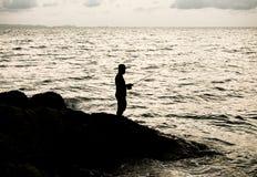 Silhueta do pescador pelo mar no nascer do sol Engodo da foto do vintage Fotos de Stock