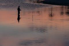 Silhueta do pescador unrecognisable no lago Imagem de Stock Royalty Free