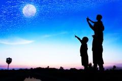Silhueta do ponto da mão do uso do pai seu olhar do filho na Lua cheia Foto de Stock Royalty Free
