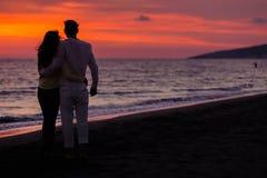 Silhueta do por do sol de pares novos no amor que abraça na praia Foto de Stock Royalty Free