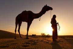 Silhueta do por do sol de uma mulher e de seu camelo. Imagem de Stock