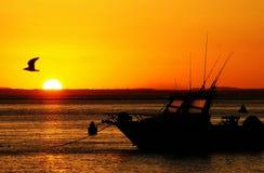 Silhueta do por do sol e do barco fotos de stock