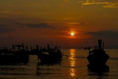 Silhueta do por do sol do barco da cauda longa na baía do mar em Tailândia Fotos de Stock Royalty Free