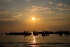 Silhueta do por do sol do barco da cauda longa na baía do mar em Tailândia Fotografia de Stock