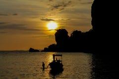 Silhueta do por do sol do barco da cauda longa na baía do mar em Tailândia Fotografia de Stock Royalty Free