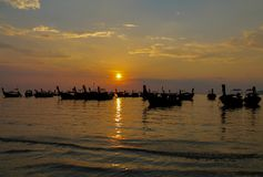 Silhueta do por do sol do barco de pesca na baía do mar em Tailândia Imagem de Stock