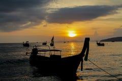 Silhueta do por do sol do barco de pesca na praia do mar em Tailândia Foto de Stock Royalty Free