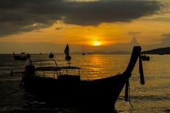 Silhueta do por do sol do barco na baía do mar em Tailândia Foto de Stock