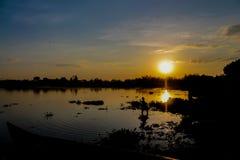 Silhueta do por do sol de uma posição na menina da água na costa do lago Imagem de Stock Royalty Free