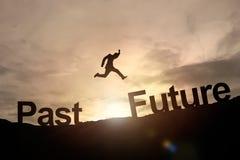 Silhueta do salto de incandescência do homem de negócios perto ao futuro sucesso c Fotos de Stock Royalty Free