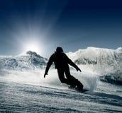 Silhueta do Snowboarder na opinião dos montes da neve Foto de Stock Royalty Free