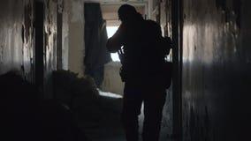 Silhueta do soldado com a arma que anda na construção durante a operação militar filme