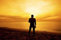 Silhueta do suporte do homem na praia no por do sol Fotografia de Stock Royalty Free