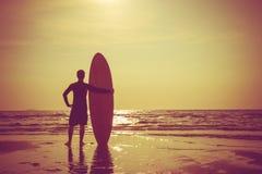 Silhueta do suporte do homem da ressaca com uma prancha Surfar no por do sol Imagem de Stock