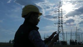 Silhueta do telefone da fala e do uso da eletricidade do coordenador durante o por do sol video estoque