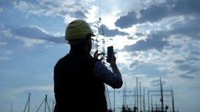 Silhueta do telefone da fala e do uso da eletricidade do coordenador durante o por do sol filme