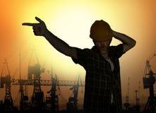 A silhueta do trabalhador que dança a emulação feliz com a pose do estrela pop do capacete de segurança que comemora o dia útil a fotografia de stock royalty free