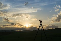 Silhueta do tripé durante o por do sol colorido fotografia de stock royalty free