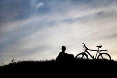 Silhueta do turista e da bicicleta no fundo do céu Fotografia de Stock
