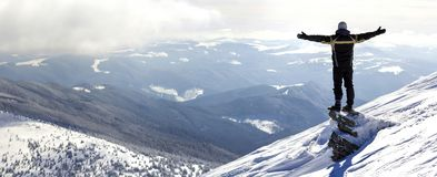 Silhueta do turista sozinho que está na parte superior nevado da montanha nos wi foto de stock royalty free