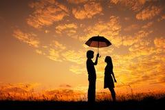 Silhueta do Valentim do homem e da mulher que guardam o guarda-chuva no por do sol da noite imagem de stock