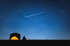Silhueta do viajante que acampa na montanha e no céu noturno com estrelas Fundo do espaço fotos de stock royalty free