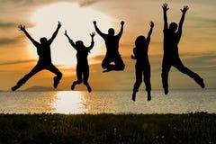 Silhueta dos amigos e dos trabalhos de equipa que saltam na praia durante o tempo do por do sol para o negócio do sucesso fotografia de stock royalty free