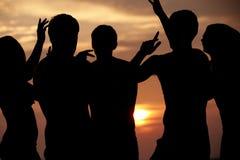 Silhueta dos amigos que têm o partido da praia Fotografia de Stock Royalty Free