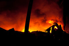 Silhueta dos bombeiros que lutam um incêndio raging com chamas enormes Foto de Stock Royalty Free