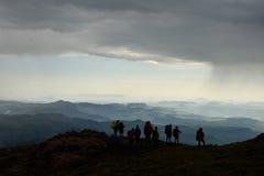 Silhueta dos caminhantes que olham montanhas e vales Fotografia de Stock Royalty Free
