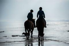 Silhueta dos cavaleiros nos cavalos de equitação da praia fotografia de stock