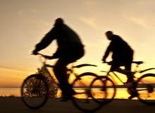 Silhueta dos ciclistas no nascer do sol Imagem de Stock Royalty Free