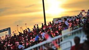 Silhueta dos espectadores que acenam bandeiras nacionais durante o ensaio 2013 da parada do dia nacional (NDP) Imagem de Stock