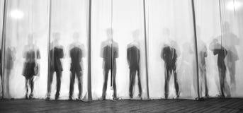A silhueta dos homens atrás da cortina no teatro na fase, a sombra atrás das cenas é similar ao branco e ao bla foto de stock