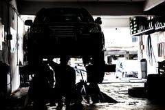 Silhueta dos mecânicos que prestam serviços de manutenção a carros em uma oficina pequena Fotografia de Stock Royalty Free